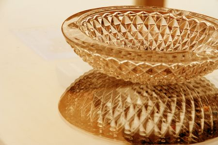 glass crystal ash tray on a reflective table surface