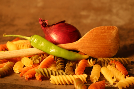 Three-colored pasta with cooking spoon on stone background