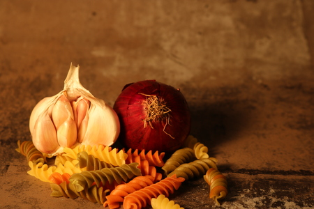 Pasta with ingredients on stone background Stock Photo