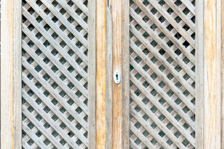 latticework: Door of a country house sithe latticework and keywhole