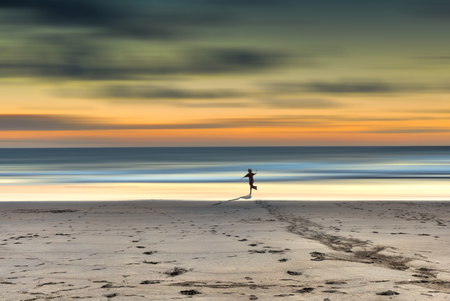 babyhood: A child runs toward the sea at sunset in a loneliness beach