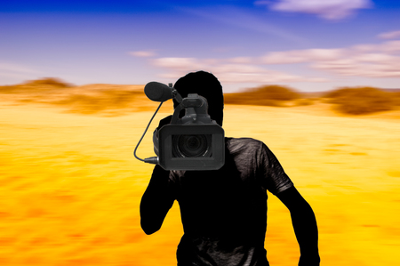 cameraman: Silhouette of a cameraman in a colored motion-blurred desert background