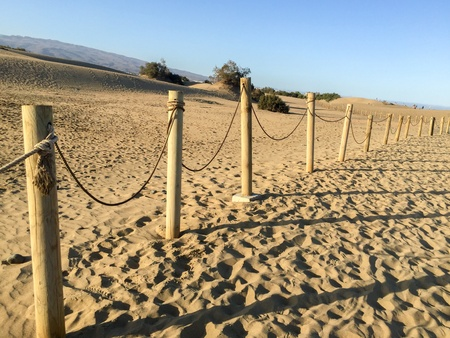 fence: A shot of a fence Between dunes in the sand of a beach Stock Photo