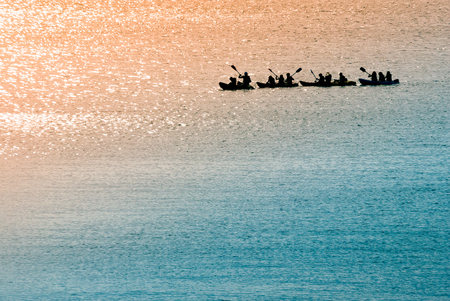 dugout: A shot of a group of canoeists rowing in the sea early in the morning Stock Photo