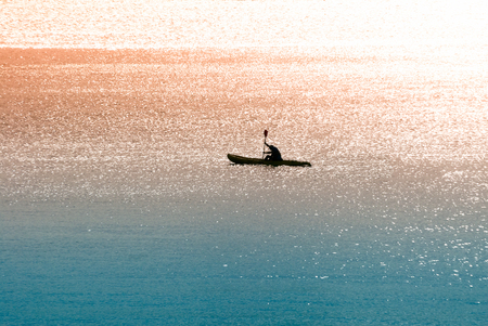 A shot of a canoeist rowing in the sea early in the morning
