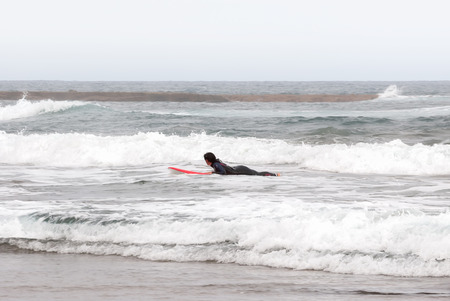 A shot of a surfer girl lying on his board between waves