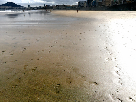 A shot of footprints on the sand of a beach at low tide and the figures of people walking in the distance