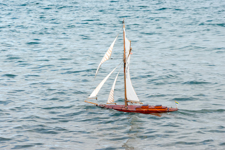 A shot of a beautiful radio controlled sailboat toy sailing in the sea Foto de archivo