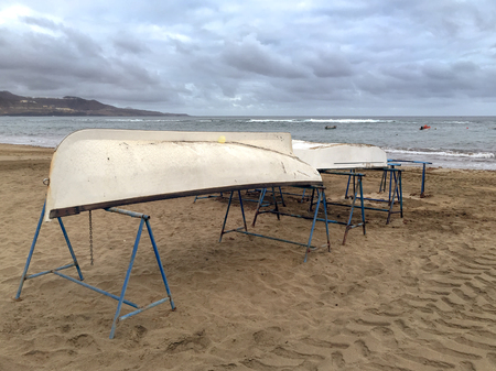 rowboats: A shot of a pair of boats on metal supports in the sand