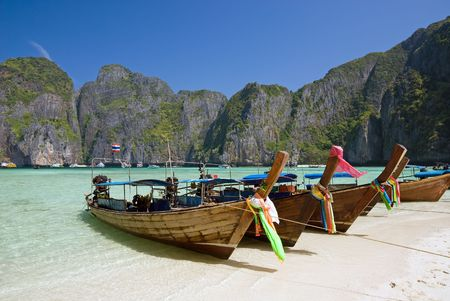 longtail: Traditional longtail boats in the famous Maya bay of Phi-phi Leh island, Krabi province, Thailand  Stock Photo