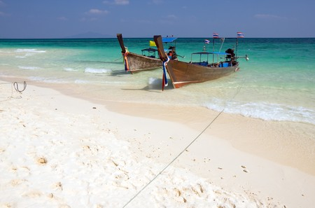 Traditional longtail boats on the white sand beach, Krabi province, Thailand photo