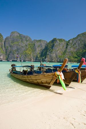 Traditional longtail boats in the famous Maya bay of Phi-phi Leh island, Krabi province, Thailand  photo
