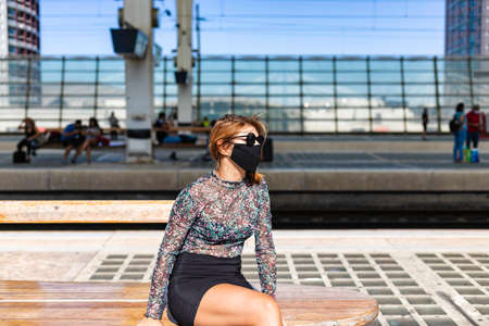 A young beautiful girl wearing the face mask is waiting for the train alone at the train station in Lisbon, Portugal