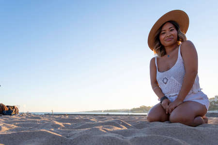 Beautiful Asian woman playing on the beach with the sand. Hippie and hipster Vietnamese girl traveling alone in Europe relaxing on the beach along the Atlantic Ocean shoreline. Woman's freedom concept