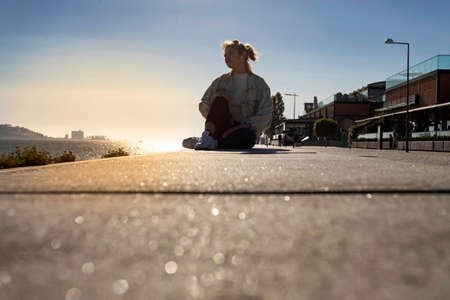 A young beautiful girl wearing a jeans jacket is sitting and relaxing along the Tejo riverside in the city center of Lisbon in Portugal. Attractive solo tourist girl traveling in Europe. Lifestyle