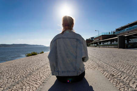 A young beautiful girl wearing a jeans jacket is sitting and relaxing along the Tejo riverside in the city center of Lisbon in Portugal. Attractive solo tourist girl traveling in Europe. Lifestyle Stock Photo