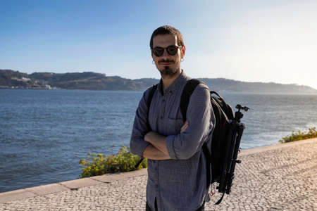 A young attractive man walking along the riverside of Tejo river in the city of Lisbon in Portugal. The April 25th bridge in the background and the district of Almeda. Only man traveling lifestyle