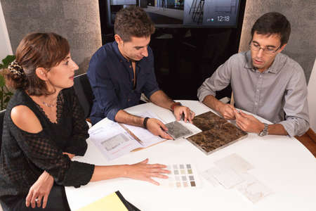 Three young architects discussing together inside a conference room the new interior design concept for a brand presentation. Young entrepreneurs working in team and looking at some project on a TV