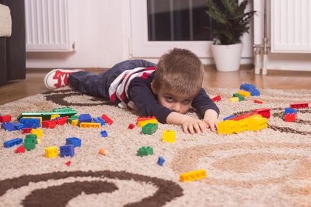 avergonzado: Ni�o acostado en el piso, mirando verg�enza, verg�enza.