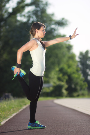 arm up: Girl stretching arm up, leg up, track. Stock Photo