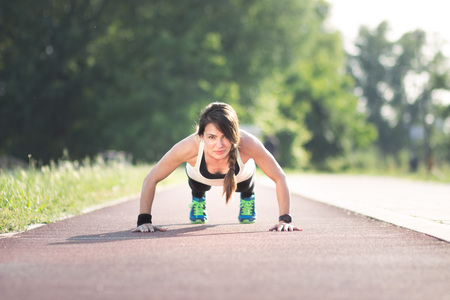 pushup: Girl push-up, outdoors, track.