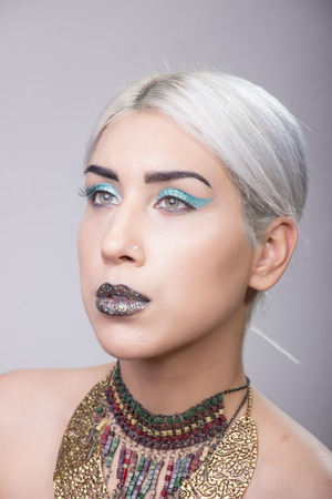 platinum hair: Young adult model Girl portrait eccentric style, shiny lips blue eyeshadow platinum hair.