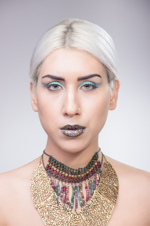 platinum hair: Young adult model Girl portrait eccentric style, shiny lips blue eyeshadow platinum hair necklace