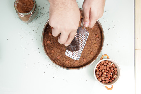 elevated view: Hand (out of focus) grating chocolate on top of chocolate cake for decoration. Shot from above, elevated view.