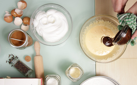 elevated view: Hand mixing chocolate with eggs, table ingredients, elevated view. Stock Photo