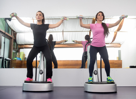 fitness trainer: Two women standing exercise weights, fitness equipment similar to Power Plate.