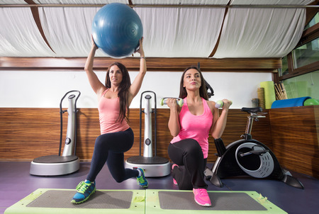 lunge: Two young women exercise gym, weights, stability ball, one leg lunge, stepper. Stock Photo