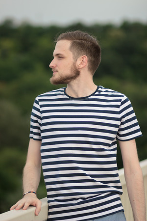 squinting: Upper body shot, young man outdoors looking sideways. Squinting eyes. Background out of focus.