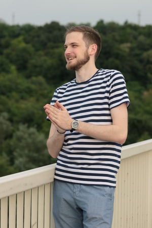 squinting: Young man looking outdoors, praying hands. Squinting eyes. Background out of focus.