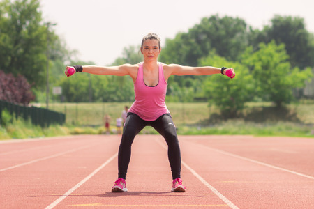squat: Girl athlete squat weights running track red
