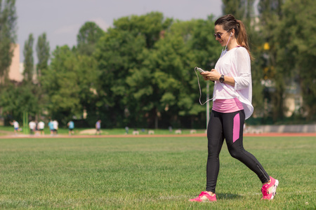 ropa casual: Young athletic girl walking grass. Casual sport clothes