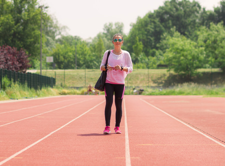 sport clothes: Athletic girl walking red sport running tracks. Casual sport clothes.