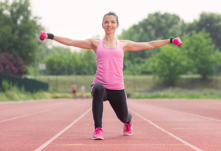 arms up: Split Squat arms up weights girl outdoors Stock Photo