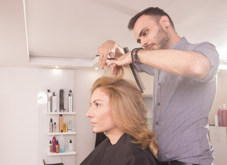 side view: side view, hairdresser cutting woman hair scissors