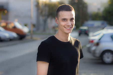 Young man in early 20s smiling portrait outdoors. Shallow depth of field, blur out od focus background.