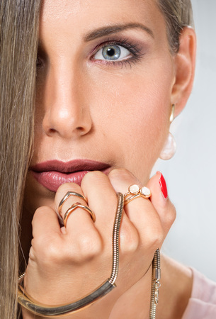 face close up: Beauty young woman face head close up jewelry necklace gold hand Stock Photo