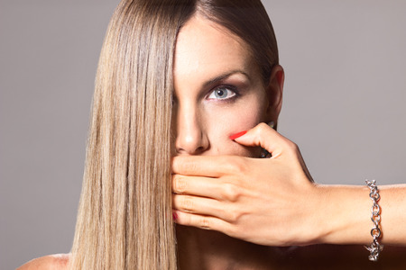 mouth close up: Close up beauty young woman hand covering mouth long hair covering half face
