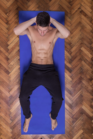 laying abs exercise: Young fit slim muscular abs man exercise elevated view. laying mat