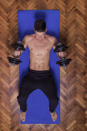 laying abs exercise: Young man abs dumbbell elevated view