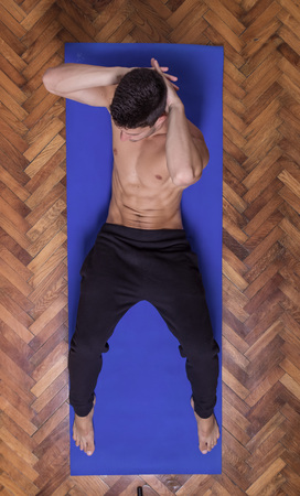 laying abs exercise: Young fit slim muscular sideway abs man exercise elevated view. laying mat Stock Photo
