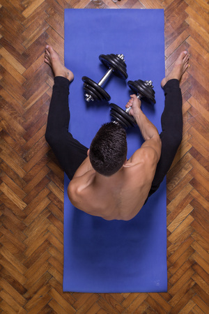 laying abs exercise: Young man elevated view taking grabbing weights strong back muscles