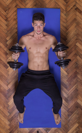 laying abs exercise: Beautiful young man fit slim fitness model dumbbell chest weights elevated view face looking at to camera Stock Photo