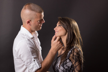 20 years old: Young couple 20 years old kissing boy girl man woman black background hand on girl face head smiling