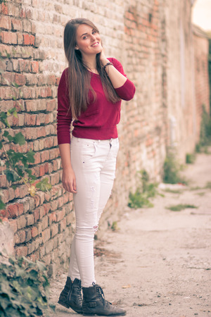 washed out: Young girl posing brick wall retro colors washed out warm tones Stock Photo