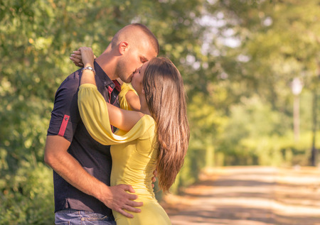 20s: young adult 20s couple kissing outdoors sunny day profile side view