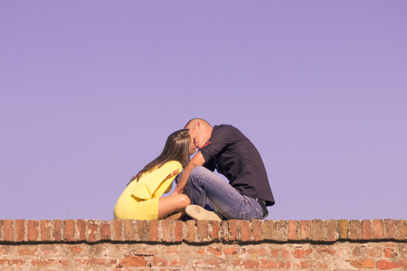 20's: young couple 20s kissing sitting brick wall